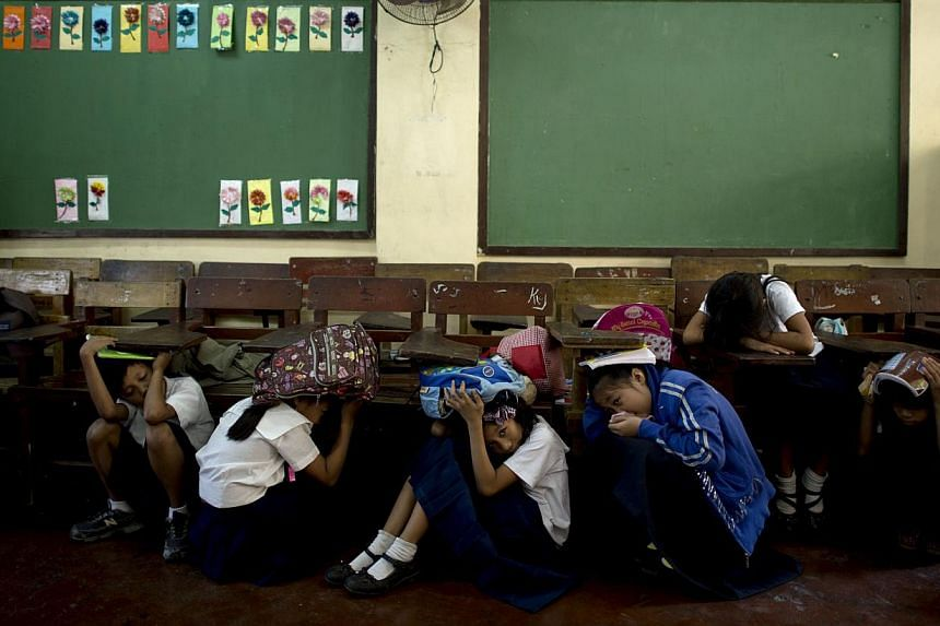 Students of Bagong Silangan Elementary school cover their head during an earthquake drill in Manila on March 19, 2014. A series of moderate earthquakes and aftershocks hit the Philippines early Sunday, with US geologists estimating the shallowest –