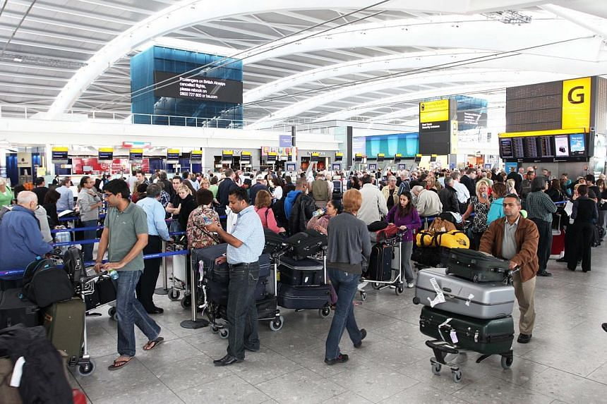 "Passengers line up for information at Terminal 5 at Heathrow Airport in London, UK, on Thursday, April 15, 2010. British police arrested two people at Heathrow airport on Saturday on suspicion of ""terrorism"" -related activities in Syria, they said."