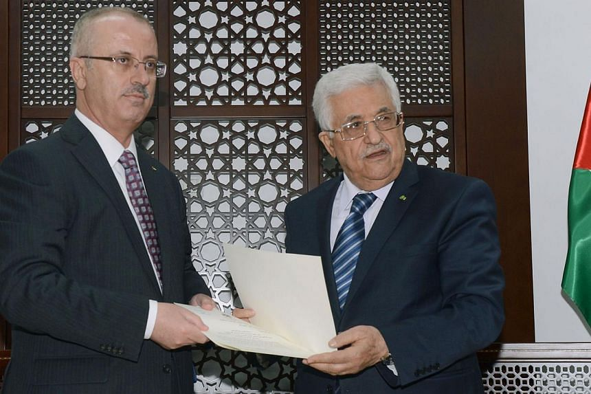 A handout picture released by the Palestinian president's office shows Palestinian president Mahmud Abbas (right) meeting with Palestinian premier Rami Hamdallah in the West Bank city of Ramallah to hand over an agreement for Hamdallah to head the co