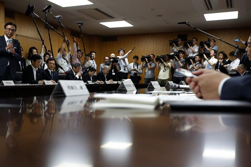 Japan's Minister-in-Charge of the Abduction Issue and head of the national public safety commission Keiji Furuya (left) speaks to the family members of victims kidnapped by North Korea, in Tokyo on May 30, 2014. -- PHOTO: REUTERS
