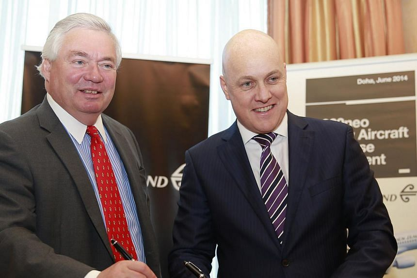 Airbus chief operating officer John Leahy (left) and Air New Zealand chief executive Chistopher Luxon pose in front of a scale model of a A320neo during a news conference in Doha on June 1, 2014. Air New Zealand said on Sunday that it has placed an o