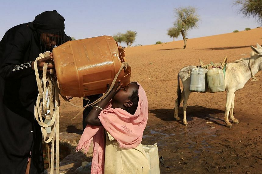 A girl is helped by her sister as she drinks water in Mellit town in North Darfur on March 24, 2014.Singaporeans can now help people in regions such as Africa, South Asia and Central America get clean water and sanitation, just by making an onl