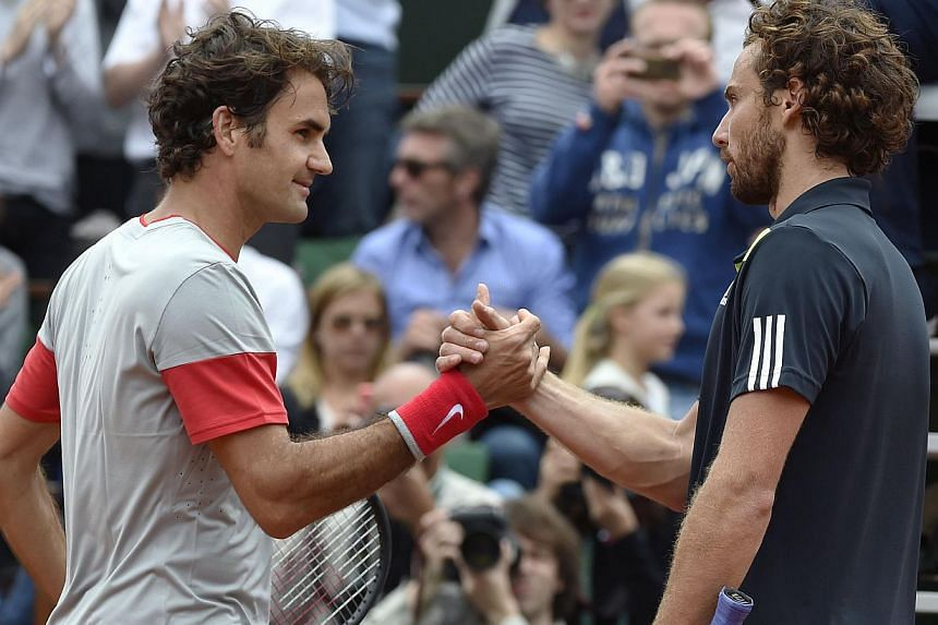 Latvia's Ernests Gulbis (right) shakes hands with Switzerland's Roger Federer at the end of their French tennis Open round of 16 match against at the Roland Garros stadium in Paris on June 1, 2014. Federer crashed to his earliest French Open defeat s