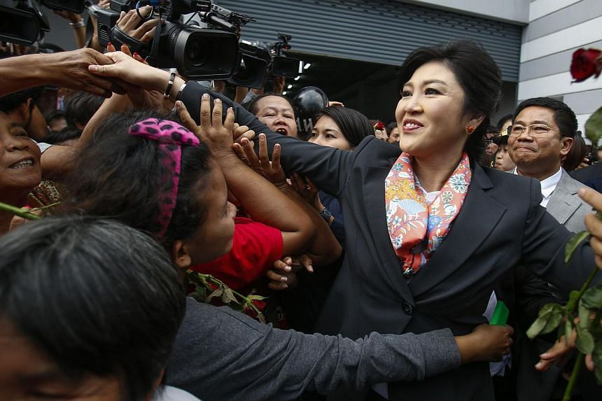 Thailand's Prime Minister Yingluck Shinawatra greets her supporters as she leaves the Permanent Secretary of Defence office in Bangkok on May 7, 2014.Thailand's former Prime Minister Yingluck Shinawatra on Sunday expressed her gratitude to supporters