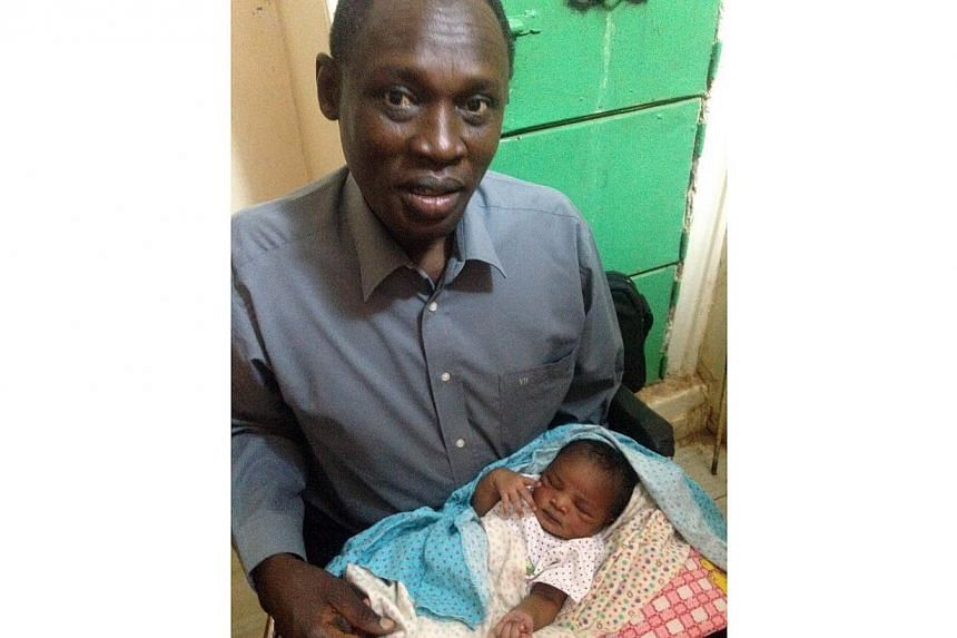 A handout picture taken on May 28, 2014, and released by the family on May 30, shows Daniel Wani, a US citizen originally from South Sudan, carrying his newborn daughter Maya at the womens prison in Khartoum's twin city of Omdurman. -- PHOTO: AFP