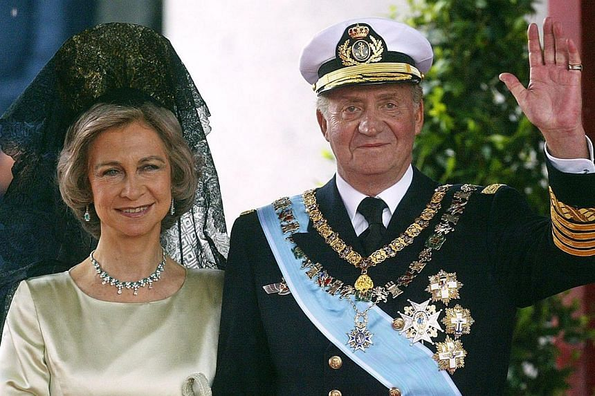 King Juan Carlos of Spain waving to photographers next to his wife Queen Sofia as they leave Madrid's Almudena Cathedral at the end of the wedding of Spanish Crown Prince Felipe and former journalist Letizia Ortiz on May 22, 2004.Spain's King J