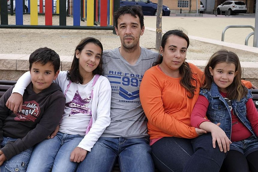 Patricia Martin (second, right) pose wtih her husband (centre) and children on a bench near their home in Vallecas, a neighborhood of Madrid on May 21, 2014. -- PHOTO: AFP
