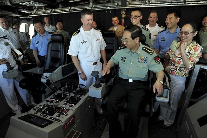 China's General Fang Fenghui (seated), chief of the general staff of the People's Liberation Army, being shown around the USS Coronado by Commander Shawn Johnston, in California last month. More than half of thought leaders polled in 11 Pacific Rim e