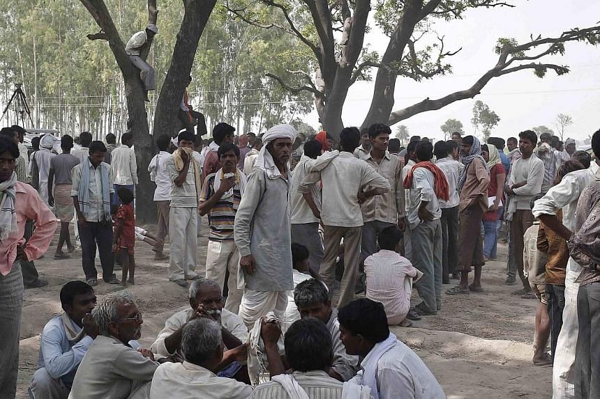 Onlookers stand at the site where two teenage girls, who were raped, were hanged from a tree at Budaun district in the northern Indian state of Uttar Pradesh on May 31, 2014. -- PHOTO: REUTERS