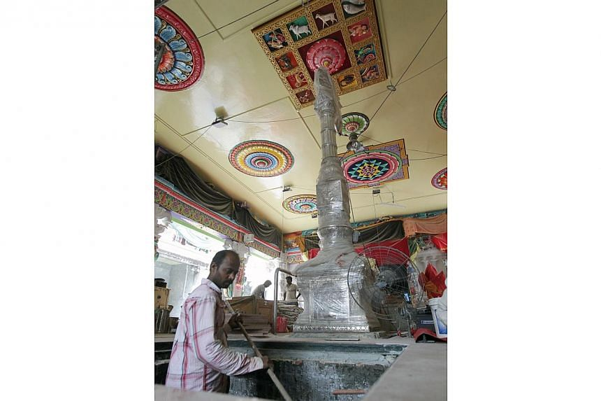 Workers inside the main hall of the Sri Veeramakaliamman temple along Serangoon Road while it was undergoing renovation and restoration works. Seen in the centre is a unique silver flag post (currently wrapped in plastic sheets to protect it) which s