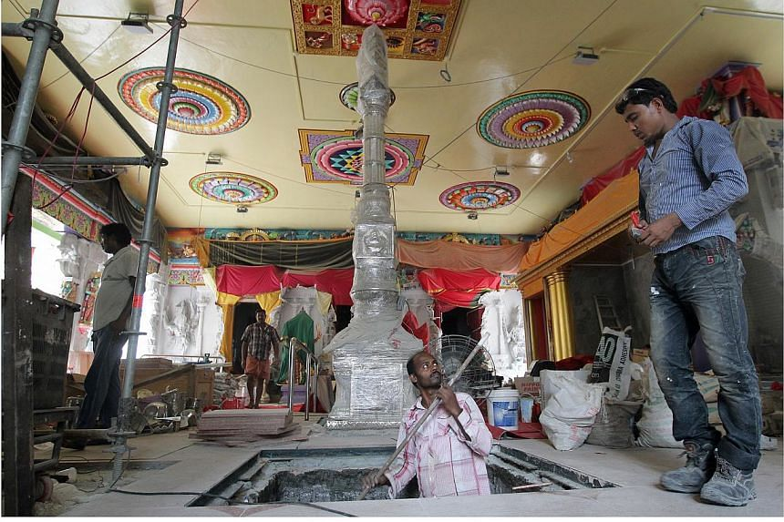 Workers inside the main hall of the temple working around Sri Veeramakaliamman's unique silver flag post.-- ST PHOTO: NEO XIAOBIN