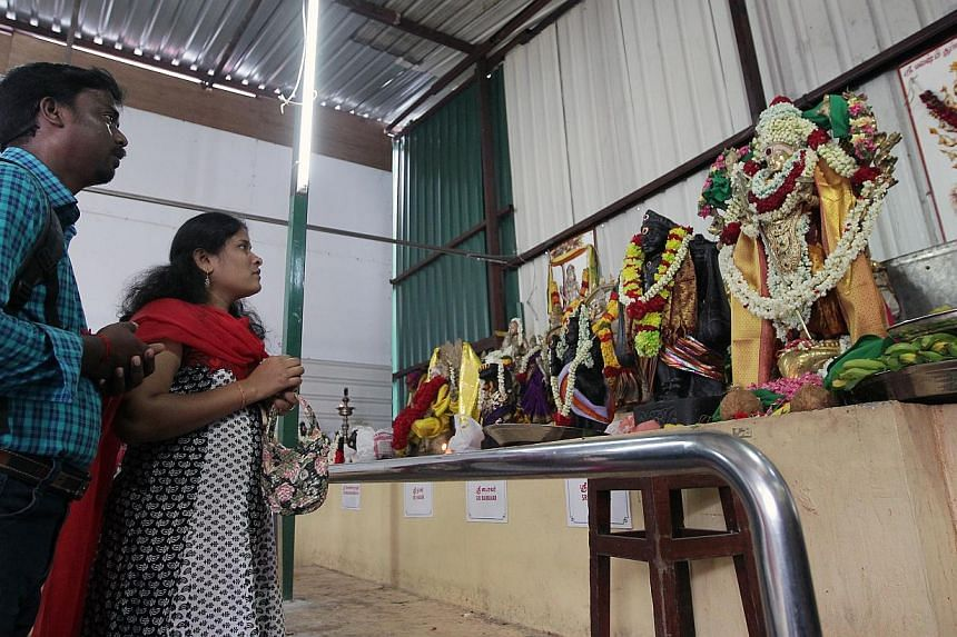Members of the public and devotees pay their respects at a makeshift prayer hall next to the current Sri Veeramakaliamman temple undergoing renovation and restoration. -- ST PHOTO: NEO XIAOBIN