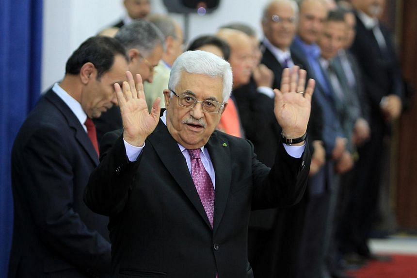 """Palestinian president Mahmud Abbas (centre) waves during the swearing-in ceremony of the new Palestinian unity government in the West Bank city of Ramallah on June 2, 2014.Palestinian president Mahmud Abbas hailed the """"end"""" of Palestinian divis"""
