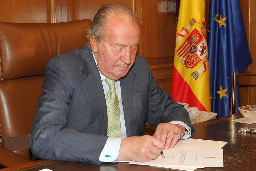 Spain's King Juan Carlos signs his abdication at the Zarzuela Palace, on June 2, 2014. -- PHOTO: REUTERS