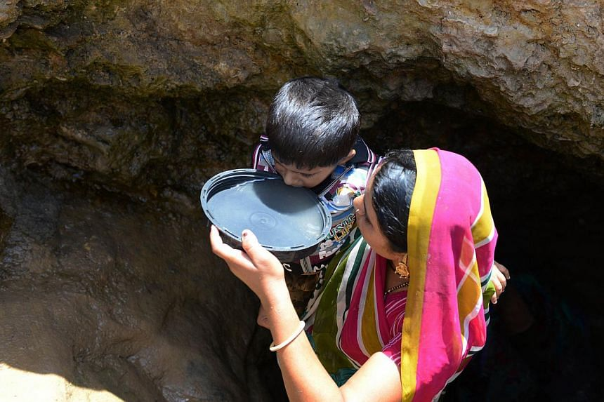 An Indian villager offers drinking water collected from a man-made well to her son in the Sujangadh village of Surendranagar district, some 160 kms from Ahmedabad on June 1, 2014. Two important water events are taking place in Singapore over the