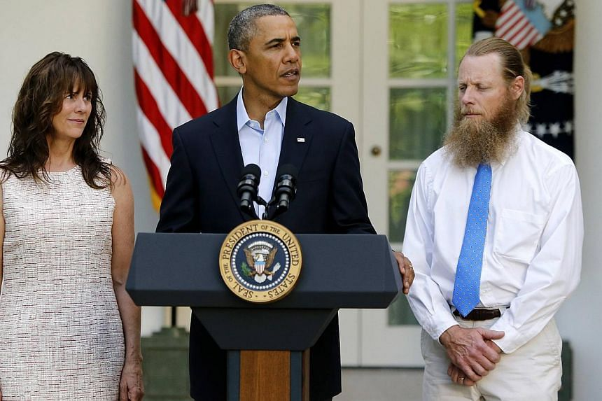 U.S. President Barack Obama stands with Bob Bergdahl (right) and Jami Bergdahl (left) as he delivers a statement about the release of their son, prisoner of war U.S. Army Sergeant Bowe Bergdahl, in the Rose Garden at the White House in Washington on