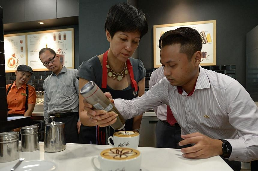 McCafe master trainer, Mohamed Hilmi, shows SMS Indranee Rajah the skills behind latte art at McCafe Training Academy at ITE College West. McDonald's opened on Monday a training cafe for Institute of Technical Education (ITE) students to give th