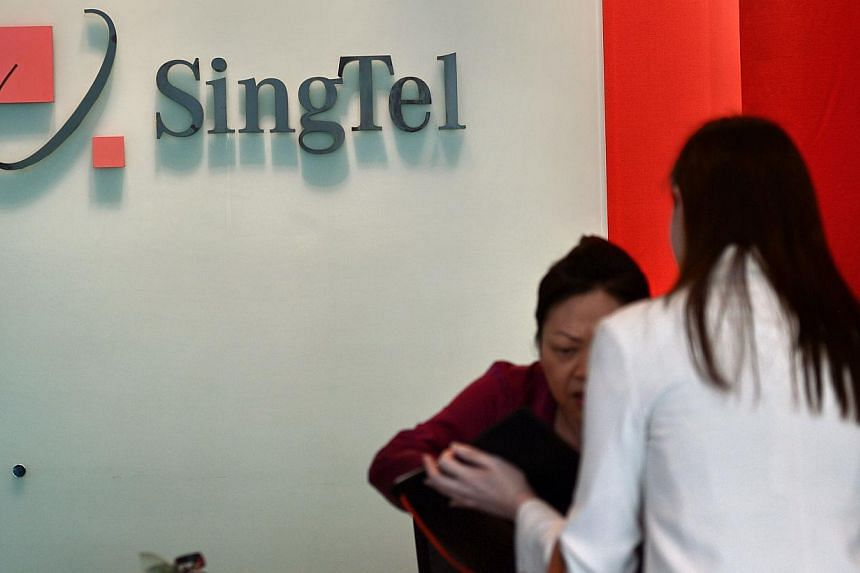 A receptionist attends to a customer at the SingTel com centre building in Singapore on May 15, 2014. -- PHOTO: AFP