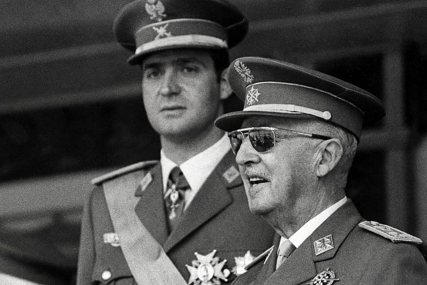 A photo taken on June 10, 1971 shows Prince Juan Carlos of Bourbon (L) and Spanish Head of State General Francisco Franco (R) attending the Victory Parade in Madrid. -- PHOTO: AFP
