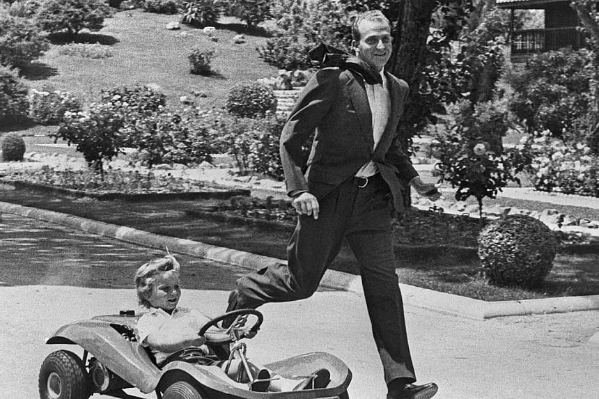 A file photo taken on October 31, 1975 shows Prince Juan Carlos of Spain playing with his son Don Felipe driving a cart, in the gardens of Zarzuela Palace in Madrid. -- PHOTO: AFP