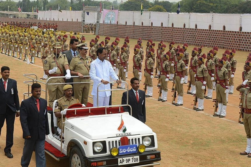 Newly-formed Telangana state's first Chief Minister K. Chandrasekhar Rao (in white) reviews a guard of honour during the state's Formation Day celebrations in Secunderabad, the twin city of Hyderabad, on June 2, 2014. -- PHOTO: AFP