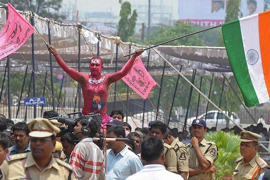 A supporter gestures while clad in body paint bearing the name of newly-formed Telangana state's first Chief Minister K. Chandrasekhar Rao during the state's Formation Day celebrations in Secunderabad, the twin city of Hyderabad, on June 2, 2014. --