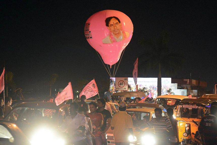 Indian supporters of Telangana hold a balloon with an image of Telangana Rashtra Samiti (TRS) president K Chandrasekhar Rao during celebrations of India's 29th state, Telangana, in Hyderabad early on June 2, 2014. -- PHOTO: AFP