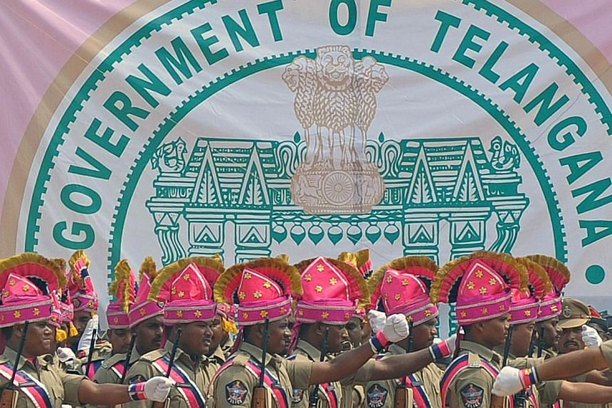 Newly-formed Telangana state policemen march past the new state's coat-of-arms during Formation Day celebrations in Secunderabad, the twin city of Hyderabad, on June 2, 2014. -- PHOTO: AFP