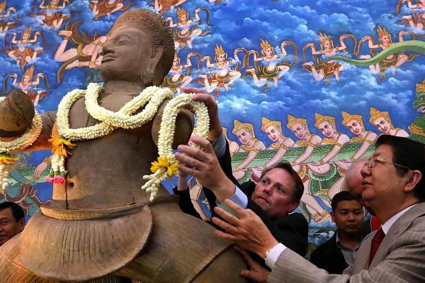 Cambodia Deputy Prime Minister Sok An (right) looks on as Jeff Daigle (left), deputy chief of mission for the US embassy in Cambodia, lays flowers at a ceremony for the return of 10th century statues in Phnom Penh on June 3, 2014 after they were welc