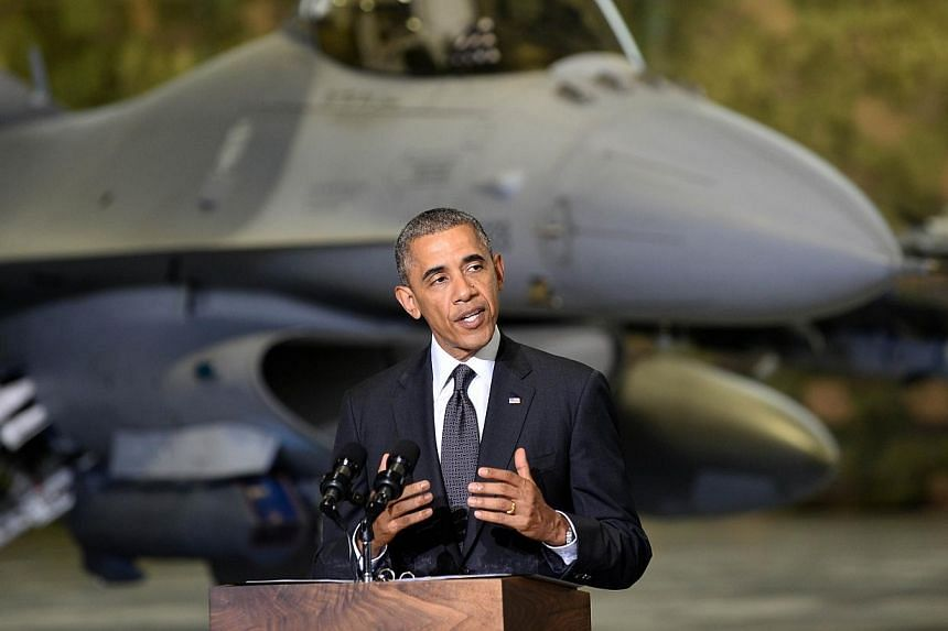US President Barack Obama addresses US and Polish airmen in front of a F-16 fighter jet in a hangar at Warsaw Chopin Airport, Poland, on June 3, 2014.Mr Obama proposed an initiative of up to US$1 billion (S$1.26 billion) to finance extra US tro
