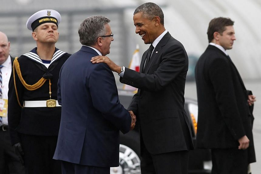 US President Barack Obama (centre, right) is greeted by Poland's President Bronislaw Komorowski upon his arrival in Warsaw on June 3, 2014. Mr Obama launched a European tour on Tuesday, June 3, 2014, shaped by the escalating separatist insurgenc