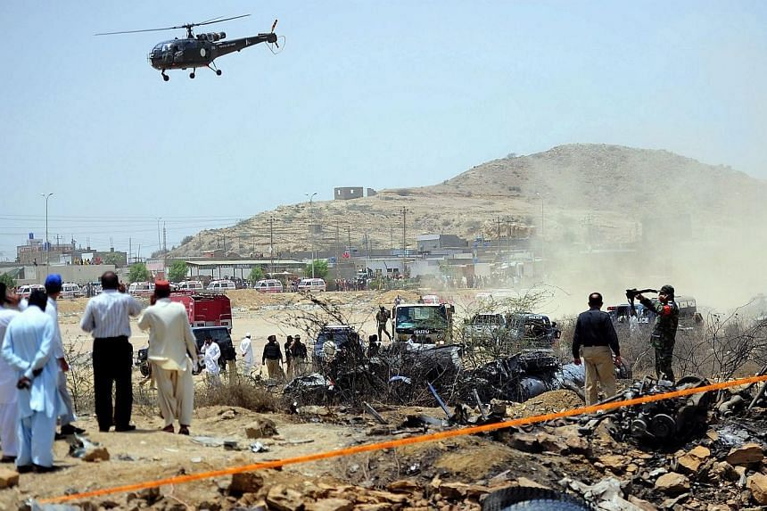 Pakistani security officials inspect the site where a Pakistan air force fighter plane crashed at a bus terminal on the outskirts of Karachi on June 3, 2014. A Pakistan air force fighter plane crashed at a bus terminal on the outskirts of Karach