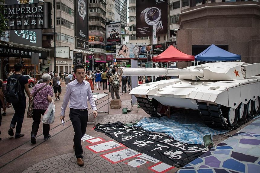 Pedestrians walk past a tank replica displayed to symbolise China's June 4, 1989 Tiananmen military crackdown in Hong Kong on June 3, 2014.Taiwan on Tuesday, June 3, 2014, urged China to face up to history and protect the rights of dissidents o