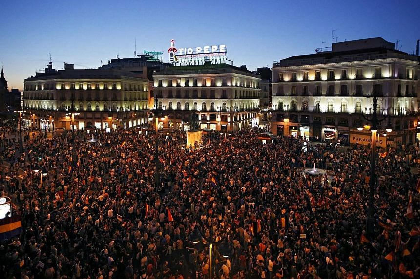 People take part in an anti-monarchist demonstration at Madrid's landmark Puerta del Sol Square, following the announcement of the abdication of Spain's King Juan Carlos, on June 2, 2014.Thousands of anti-royalists took to the streets across Sp