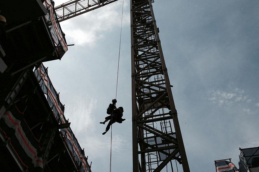 The Singapore Civil Defence Force (SCDF) rescued a 39-year-old man who was stuck on a crane at a construction site in Whampoa East on Tuesday morning. -- PHOTO:SINGAPORE CIVIL DEFENCE FORCE