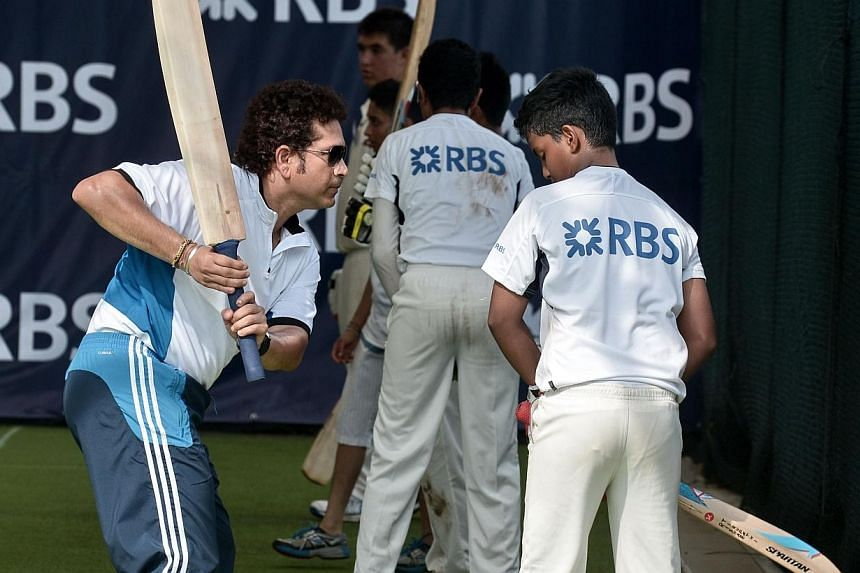 Retired Indian cricketing legend Sachin Tendulkar (left) holds a training session for young players at the Singapore Cricket Club on June 3, 2014. Tendulkar told reporters he welcomed the opportunity to play alongside West Indies great Brian Lara in
