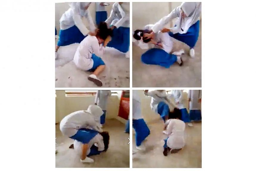 Bad behaviour: Images from the screen grab of the clip showinga schoolgirl being brutally set upon by a group of female schoolmates. -- PHOTO: THE STAR/ASIA NEWS NETWORK