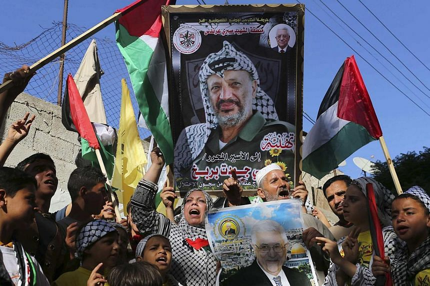 Palestinians hold pictures of late Palestinian leader Yasser Arafat (top) and Palestinian President Mahmoud Abbas as they celebrate the announcement of the unity government, in Khan Younis in the southern Gaza Strip on June 2, 2014. -- PHOTO: REUTERS