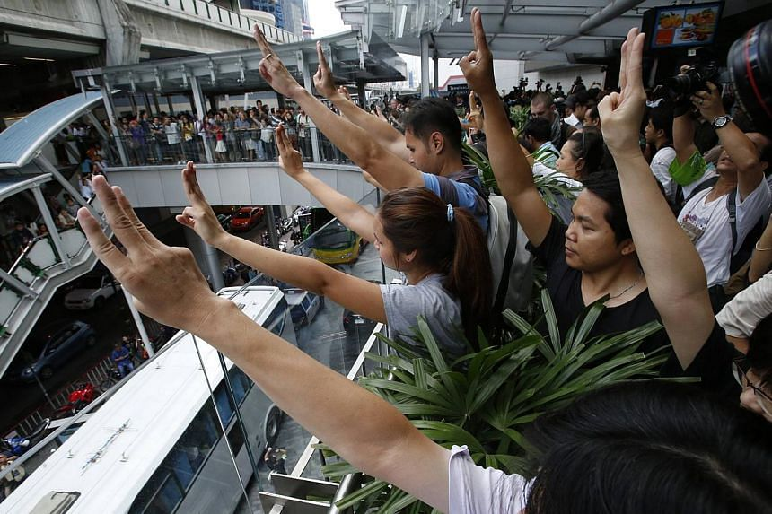 Protesters against military rule gesture by holding up their three middle fingers in the air, during a brief demonstration at a shopping mall in Bangkok on June 1, 2014. -- PHOTO: REUTERS