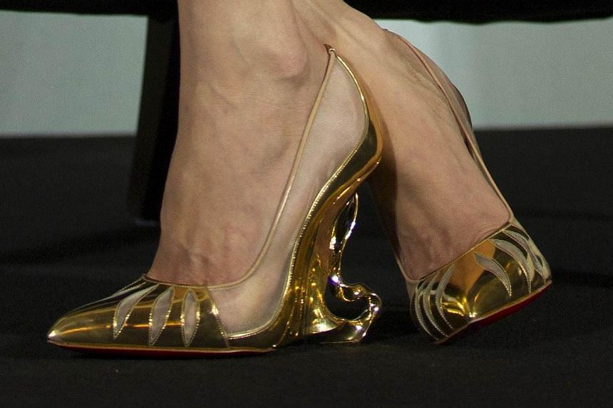 Actress Angelina Jolie was spotted wearing her custom-made gold Christian Louboutin heels while promoting Maleficent in Shanghai, China on June 3, 2014. -- PHOTO: AFP
