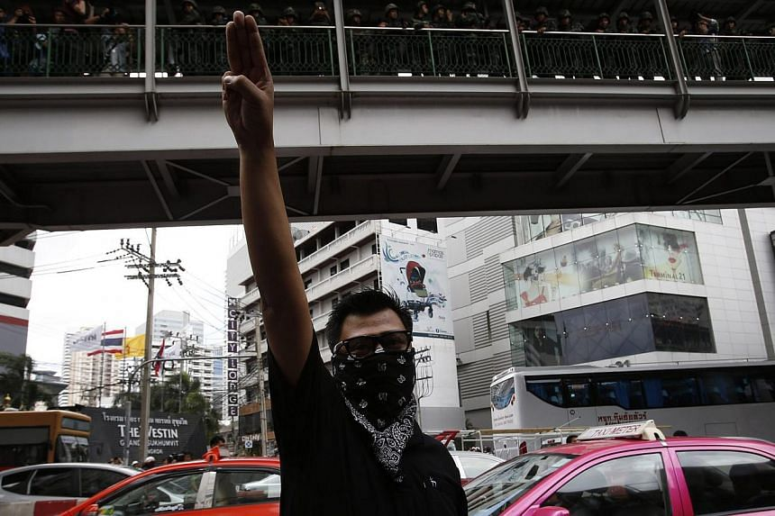 A protester against military rule gestures by holding up his three middle fingers in the air, as soldiers look on from an elevated walkway, during a brief demonstration outside a shopping mall in Bangkok on June 1, 2014. -- PHOTO: REUTERS