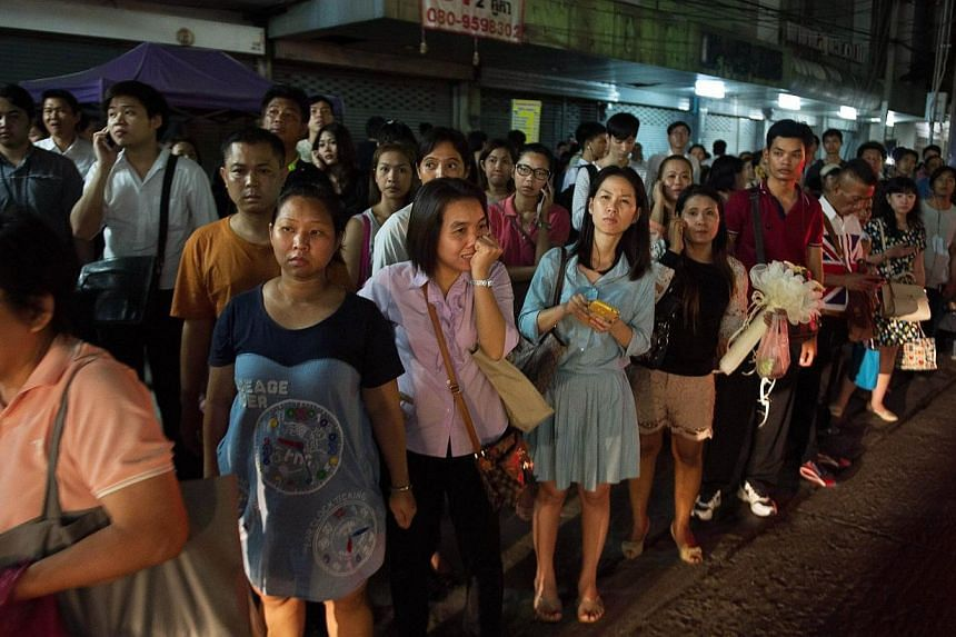 Thai commuters wait for taxis or motorbike taxis as they rush home after a curfew was imposed following the Thai army chief's announcement that armed forces were seizing power in Bangkok on May 22, 2014.Thailand's junta said on Tuesday that it