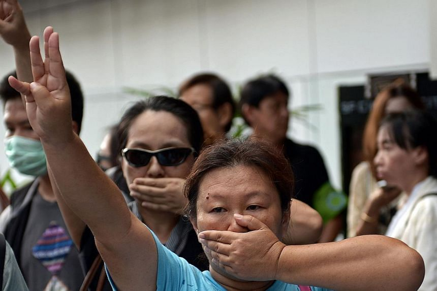 This file picture taken on June 1, 2014 shows anti-coup protesters flashing a three-finger salute during a gathering at a shopping mall which was broken up by security forces in downtown Bangkok. -- PHOTO: AFP