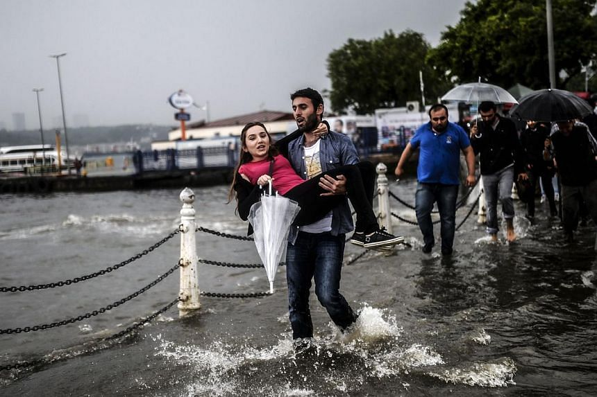 A Turkish man carries a woman through a flooded quay on June 2, 2014, at Uskudar district of Istanbul during a rainy day. -- PHOTO: AFP