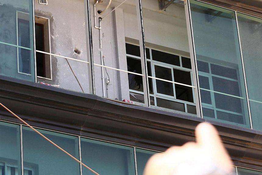 A man points at a hole on the wall of the Libyan government's head offices after it was hit by a rocket-propelled grenade on June 4, 2014 in Tripoli.A rocket hit the Libyan government's head offices, where new Prime Minister Ahmed Miitig was to