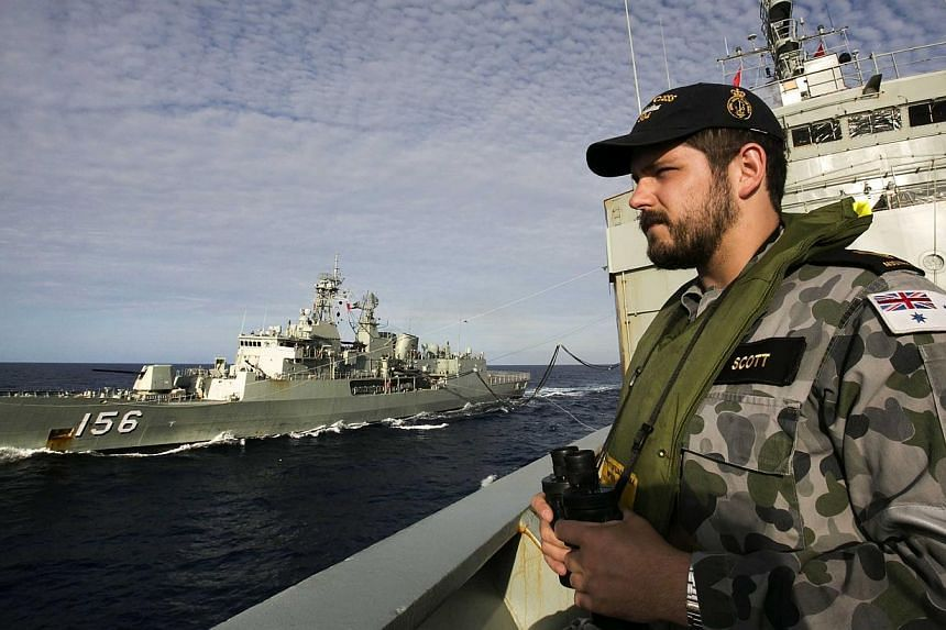 Australian Defence shows Able Seaman Maritime Logistics – Steward Kirk Scott keeping watch on the forecastle of auxiliary oiler HMAS Success as they conduct a Replenishment at Sea with HMAS Toowoomba whilst both ships are deployed in search of the