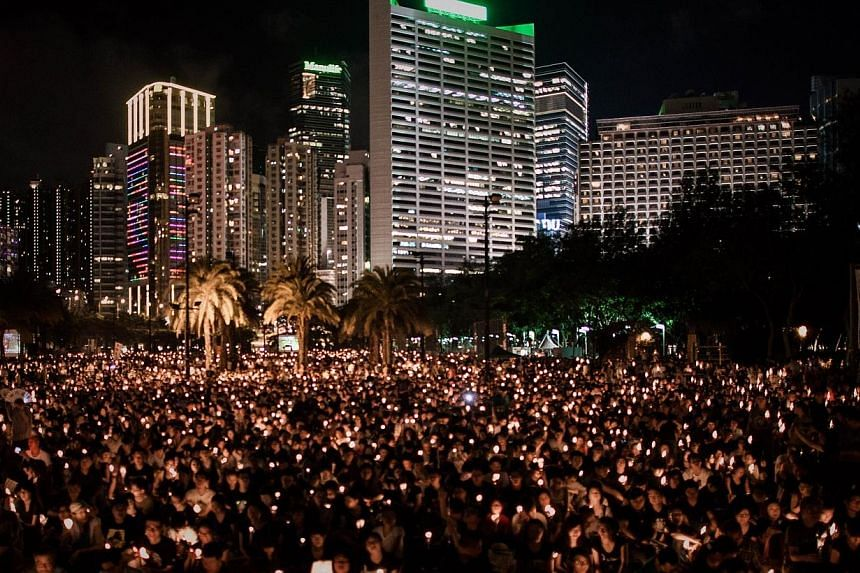 People hold candles to commemorate China's 1989 Tiananmen Square events during a candlelight vigil in Hong Kong on June 4, 2014. -- PHOTO: AFP