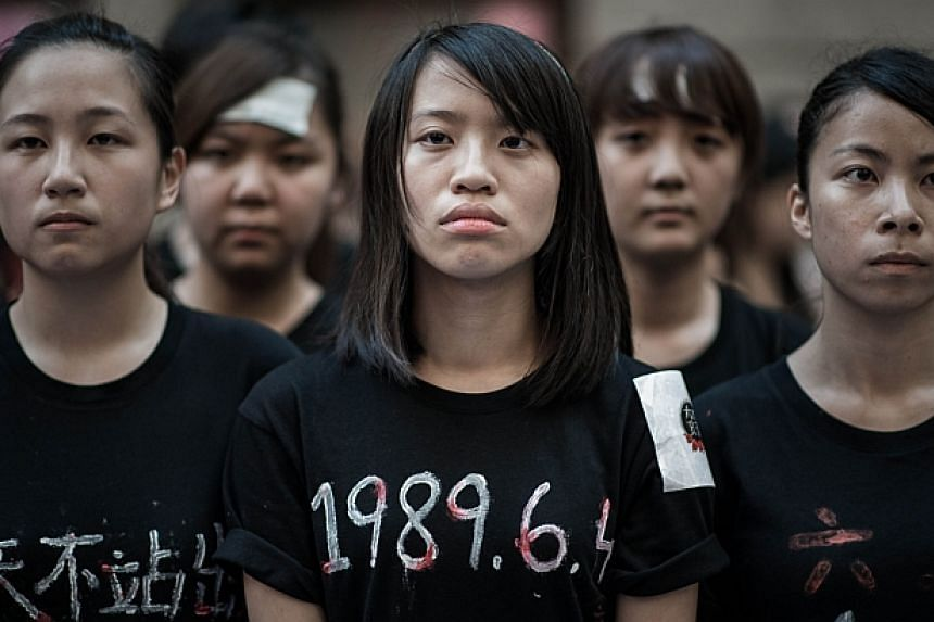 Students look on before singing to commemorate China's 1989 Tiananmen Square events ahead of a candlelight vigil in Hong Kong on June 4, 2014. -- PHOTO: AFP