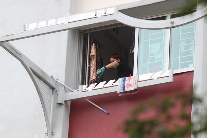 A police officer investigates the kitchen window of the sixth floor unit at Blk 105 Ang Mo Kio Avenue 4, where a woman is believed to have fallen from. Another body is believed to be in the unit. -- ST PHOTO: SEAH KWANG PENG