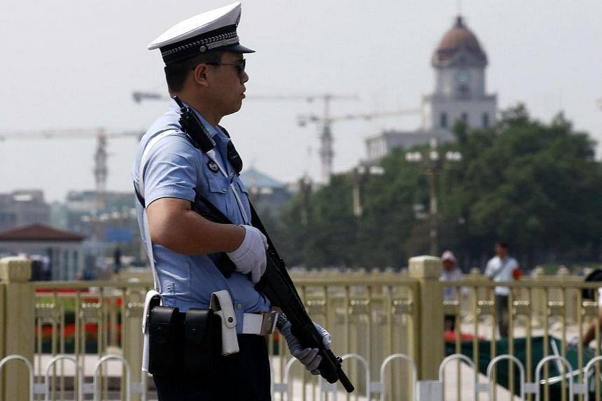 A policeman stands guard with a shotgun in front of Tiananmen Square in Beijing on June 4, 2014. -- PHOTO: REUTERS